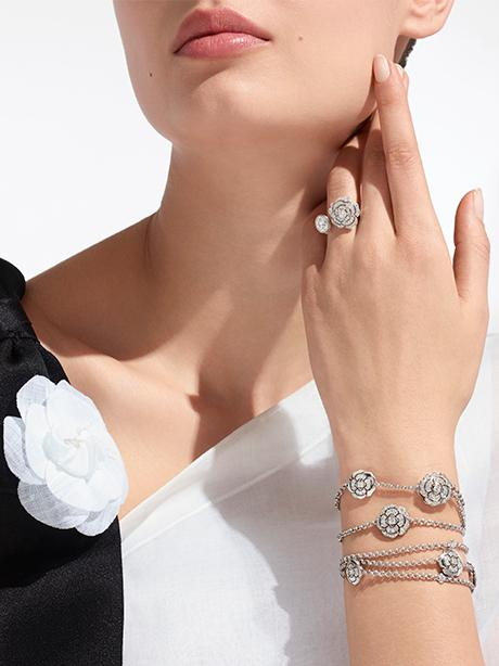 Model wearing a CAMÉLIA transformable bracelet and ring in gold and diamonds.