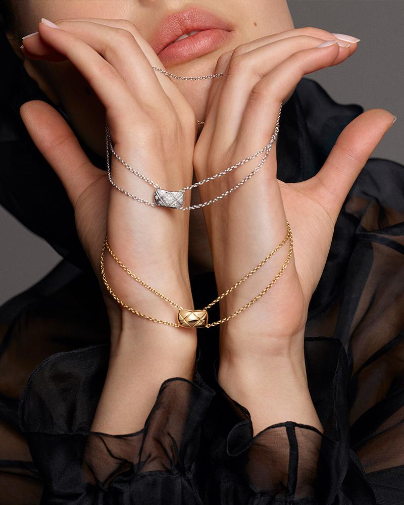 Model holding 2 COCO CRUSH necklaces in 18K BEIGE GOLD and diamonds and 18K white gold* and diamonds – Double C